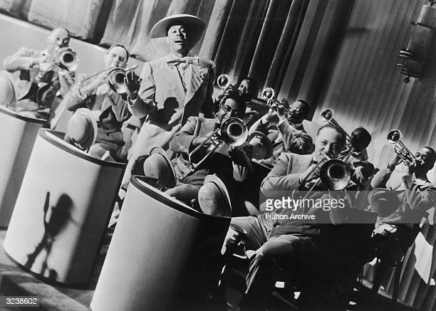 Jazz bandleader and singer Cab Calloway standing and singing amongst his orchestra The Missourians in a still from director Andrew Stone's film...