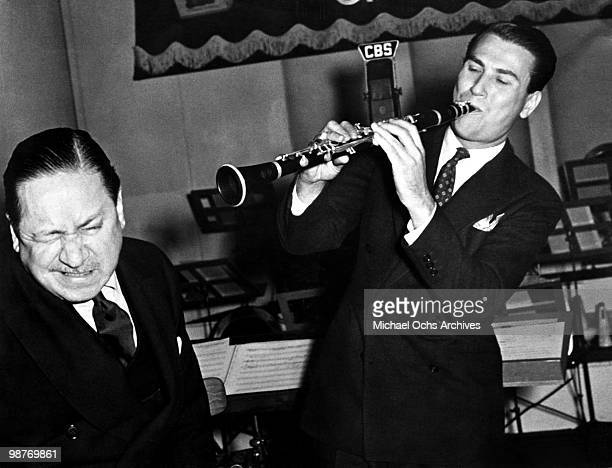Jazz clarinettist and bandleader Artie Shaw clowns around with humorist Robert Benchley during a performance on Old Gold's Radio Program circa 1940...