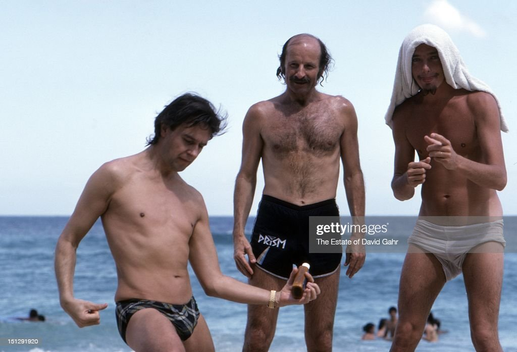 Jazz guitarist John McLaughlin, jazz keyboardist Joe Zawinul, and jazz electric bassist Jaco Pastorius pose for a fun portrait while relaxing at a beach near Havana before performing at Havana Jam, an historic three-day series of music concerts sponsored by the American music industry and the Cuban government in April 1979 in Havana, Cuba.