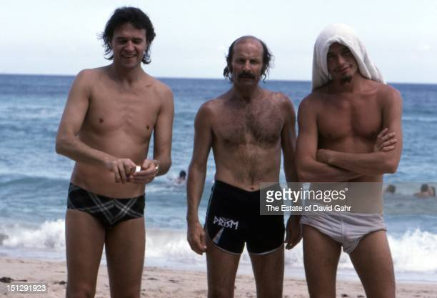 Jazz guitarist John McLaughlin, jazz keyboardist Joe Zawinul, and jazz electric bassist Jaco Pastorius pose for a portrait while relaxing at a beach...