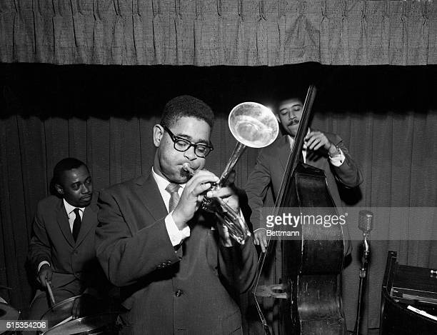 Jazz legend Dizzy Gillespie playing the trumpet with two other band members in 1955