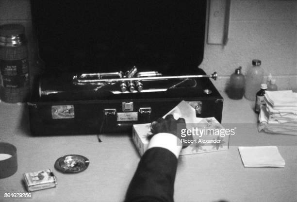 Jazz musician and singer Louis Armstrong reaches for a Kleenex tissue in his makeshift dressing room prior to performing with his band in a high...