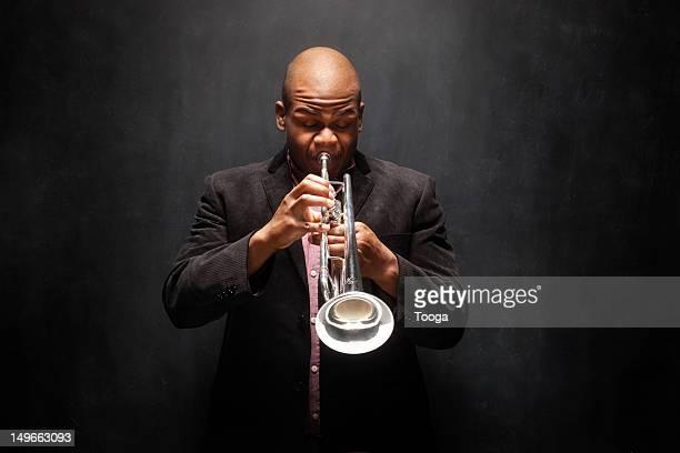 Jazz musician blowing on trumpet