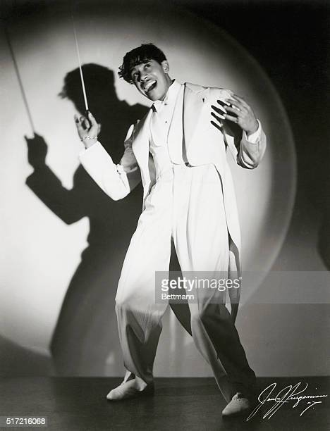 Jazz musician Cab Calloway wearing a white zoot suit and holding a baton
