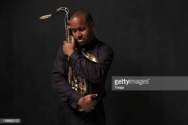 Jazz musician cradling saxophone
