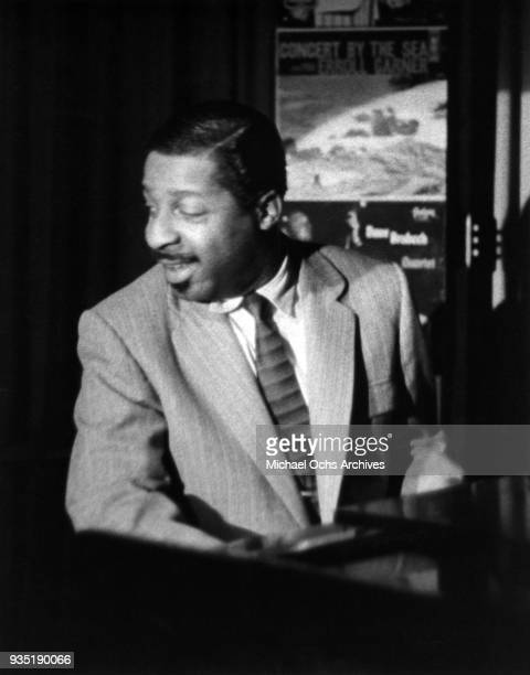 Jazz musician Erroll Garner performing at the piano in front of a poster for his album Concert by the Sea in 1955 in New York New York