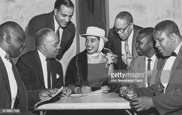 Jazz musician Harry Belafontes wife Marguerite Belafonte and a group of people smiling and having a conversation 1958