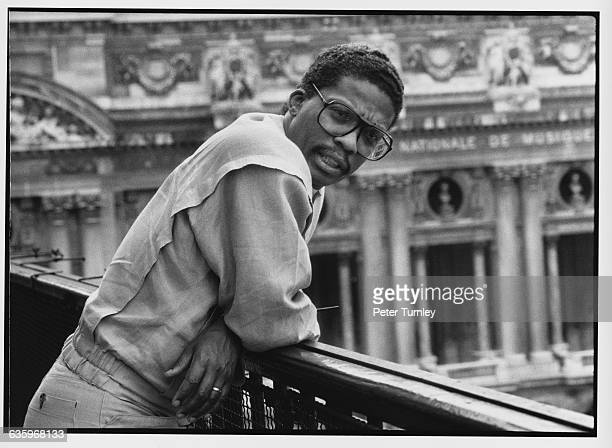 Jazz musician Herbie Hancock leans on a railing with a view of the Paris Opera House below