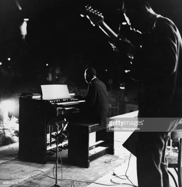 Jazz musician Jimmy Smith seated at his organ performs during an outdoor concert with guitarist Quentin Warren behind him 1960s