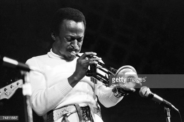 Jazz musician Miles Davis plays his trumpet onstage in circa 1975