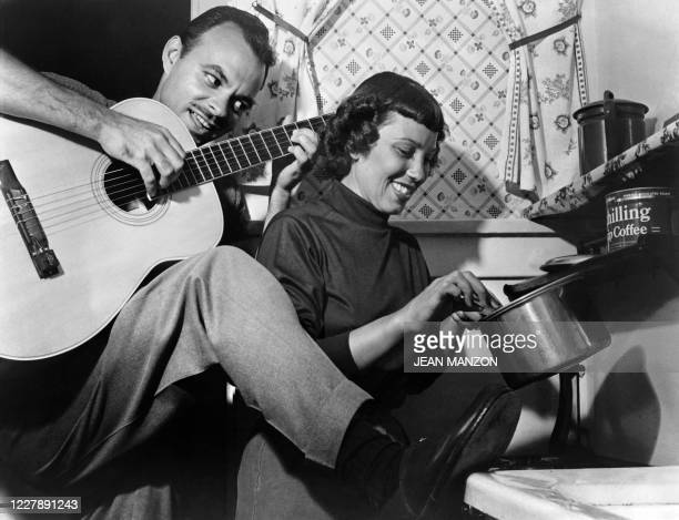 Jazz musician plays the guitar in his kitchen, while his partner prepares the meal, in 1948 in Balboa, California, where a lot of progressive jazz...