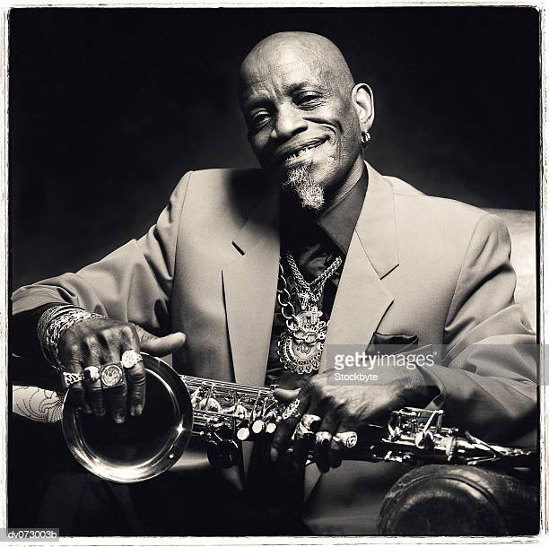 Jazz musician smiling and holding saxophone