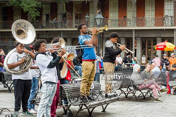 jazz musicians busk in jackson square, new orleans - new orleans french quarter stock photos and pictures