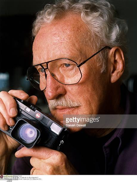 Jazz photographer William Claxton poses with a Leica camera at his home in 2000 in Los Angeles, California, United States.
