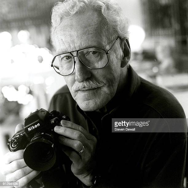 Jazz photographer William Claxton poses with his Nikon camera at his home in 2000 in Los Angeles, California, United States.