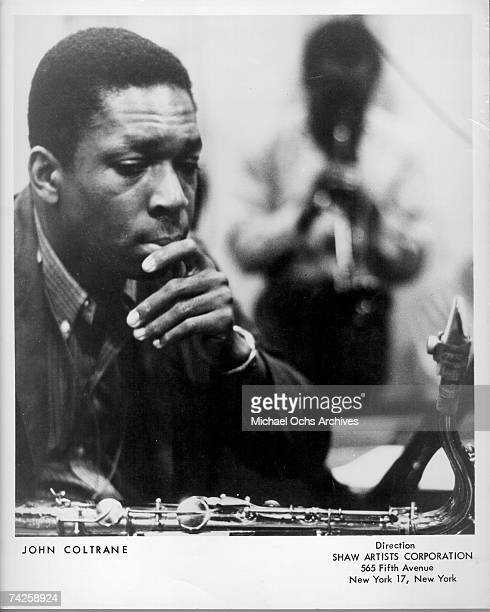 Jazz saxophonist John Coltrane listens as a man plays trumpet in the background in circa 1961