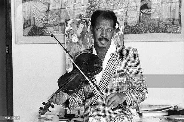 Jazz saxophonist violinist and composer Ornette Coleman poses for a portrait with his violin at home on May 28 1986 in New York City New York