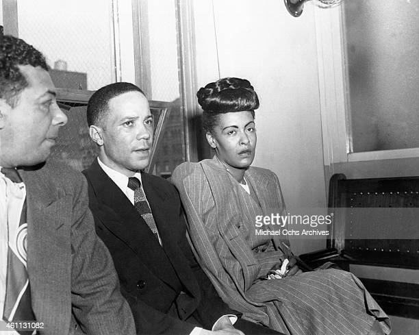 Jazz singer Billie Holiday is read the charge for heroin possession at the US Commissioners Office seated next to her are her pianist Bobby Tucker...