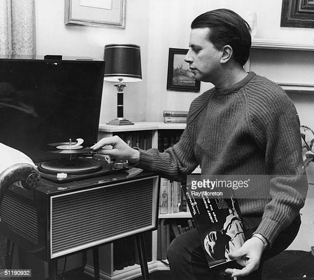 Jazz singer George Melly puts on a Jimmy Rushing record at his Chelsea home April 1960