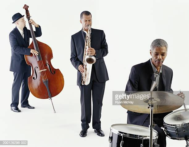 jazz trio playing saxophone, bass, and drums - performance group stock pictures, royalty-free photos & images