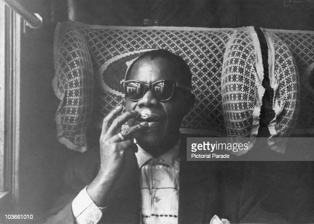 Jazz trumpeter and singer Louis Armstrong pictured moisturizing his lips while travelling on a train during his tour of France November 1955 Also...
