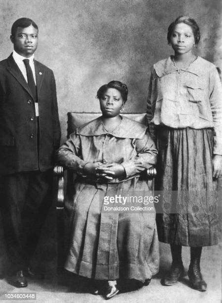 Jazz trumpeter and singer Louis Armstrong poses for a portrait with his mother Mary Albert and sister Beatrice 'Mama Lucy' Armstrong circa 1918 in...