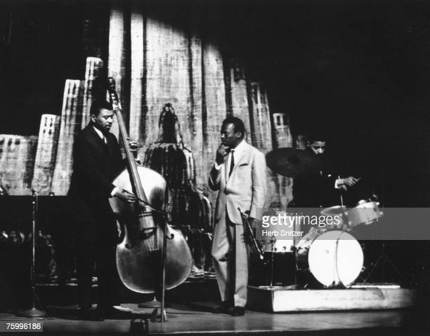 Jazz trumpeter Miles Davis performs onstage with his bass player Paul Chambers and drummer Jimmy Cobb at the Apollo Theater in 1960 in New York City...