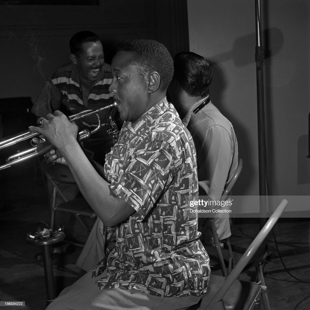Jazz trumpeter Roy 'Little Jazz' Eldridge records with the 1953 metronome All Stars as singer Billy Eckstine laughs with saxophonist Lester Young (obscured) at Fulton Studios as on June 9, 1953 in New York City, New York.