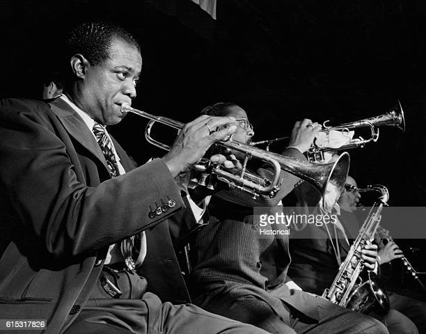 Jazz trumpeters Louis Armstrong and Roy Eldridge play with several other musicians, circa 1950.