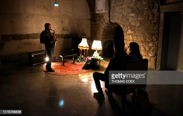 Jazzman musician Gael Horellou plays saxophone for a couple in the Jazz club La Gare in Paris on June 10 the Jazz club decided to organize small...