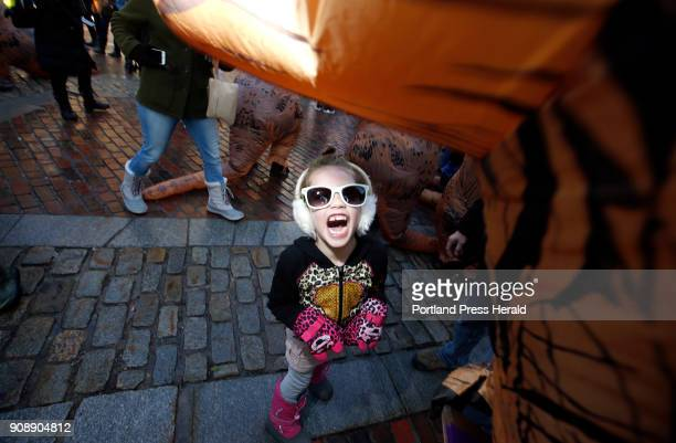 Jazzy Gray of Portland lets out a ferocious roar amid Tyrannosaurus rexcostumed people and onlookers at Monument Square on Saturday