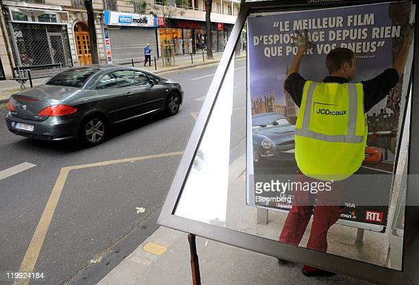 A JCDecaux employee installs an advertising poster at a bus stop in Paris France on Wednesday July 27 2011 JCDecaux is the world's secondlargest...