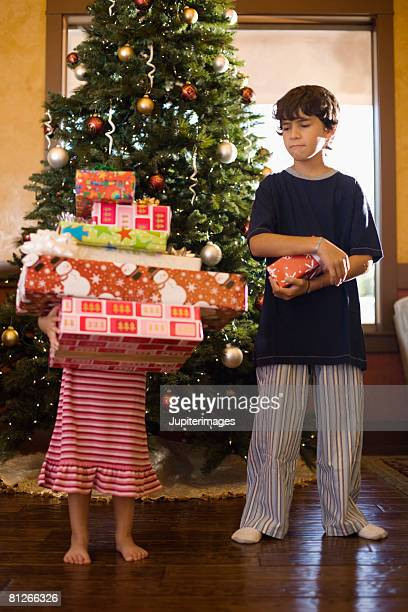 Jealous brother looking at sister's Christmas gifts