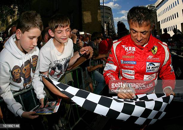 Jean Alesi of France and driver of the AF Corse Ferrari F430 GT signs autographs for fans during the parade of drivers for the 78th running of the Le...