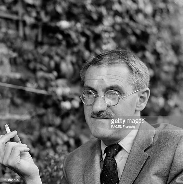 Jean Anouilh And His Daughter Catherine En 1962 portrait souriant de l' écrivain et dramaturge français Jean ANOUILH fumant une cigarette devant un...
