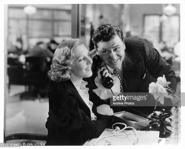 Jean Arthur and Gary Cooper listen to a phone call in a scene from the film 'Mr Deeds Goes To Town' 1936
