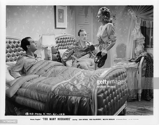 Jean Arthur brings out shoes to Fred MacMurray and Melvyn Douglas in a scene from the film 'Too Many Husbands' 1940