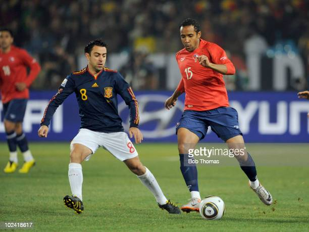 Jean Beausejour of Chile dribbles as Xavi of Spain defends during the 2010 FIFA World Cup South Africa Group H match between Chile and Spain at...