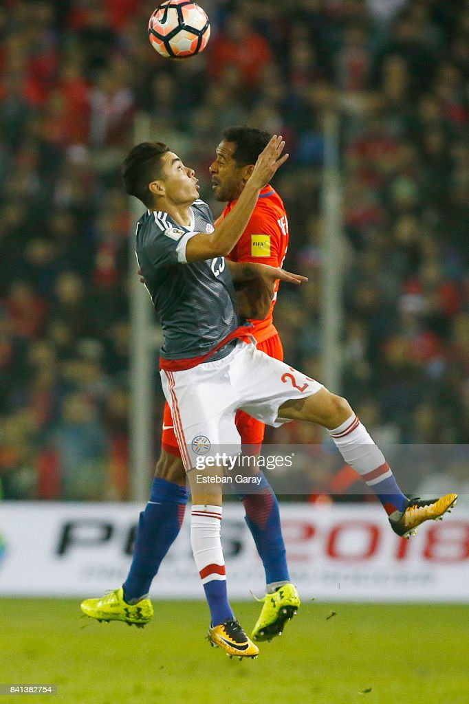 Jean Beausejour of Chile jumps for the ball with Miguel Almiron of Paraguay during a match between Chile and Paraguay as part of FIFA 2018 World Cup Qualifier at Monumental Stadium on August 31, 2017 in Santiago, Chile.