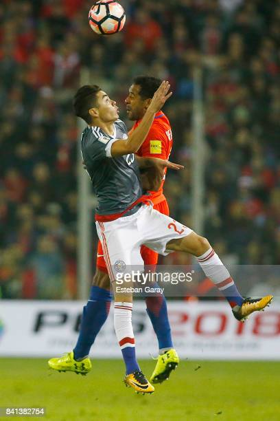 Jean Beausejour of Chile jumps for the ball with Miguel Almiron of Paraguay during a match between Chile and Paraguay as part of FIFA 2018 World Cup...
