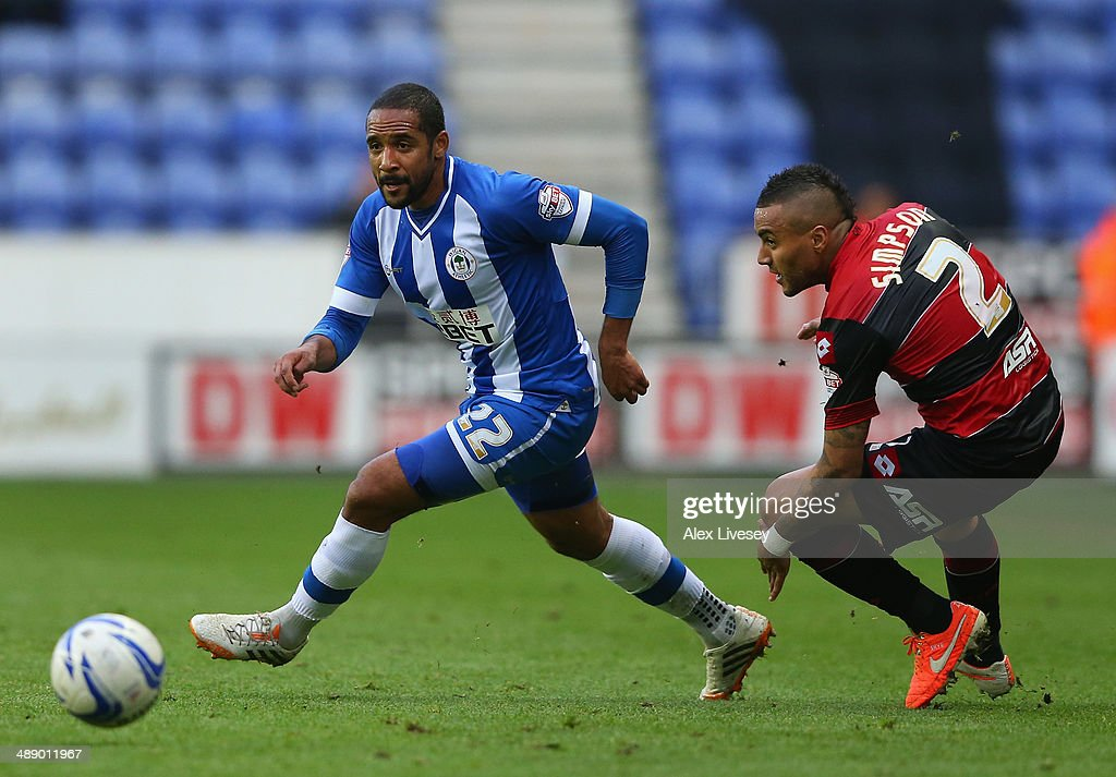 Jean Beausejour of Wigan Athletic beats Danny Simpson of Queens Park Rangers during the Sky Bet Championship Play Off Semi Final first leg match between Wigan Athletic and Queens Park Rangers at DW Stadium on May 9, 2014 in Wigan, England.