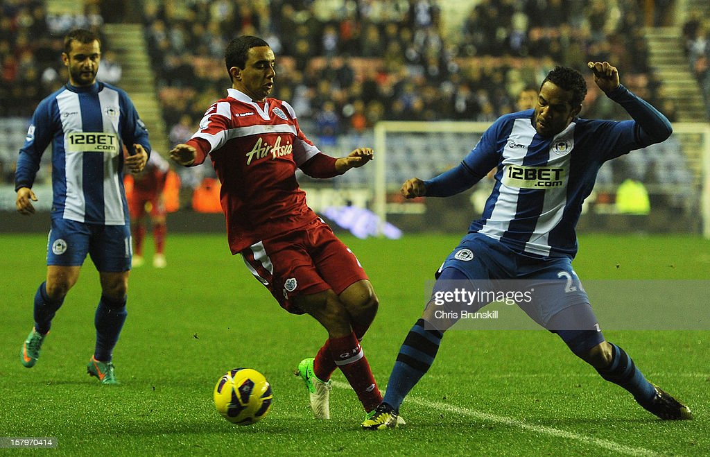 Jean Beausejour of Wigan Athletic challenges Fabio of Queens Park Rangers during the Barclays Premier League match between Wigan Athletic and Queens Park Rangers at the DW Stadium on December 8, 2012 in Wigan, England.