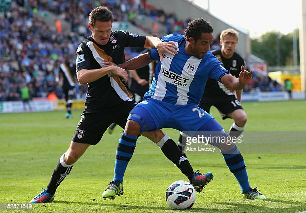 Jean Beausejour of Wigan Athletic holds off a challenge from Sascha Riether of Fulham during the Barclays Premier League match between Wigan Athletic...