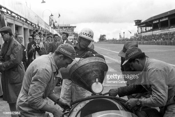 Jean Behra, Maserati 250F, Grand Prix of Germany, Nurburgring, 05 August 1956. Jean Behra helps refuel his Maserati 250F during a pit stop in the...