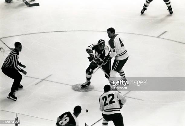 Jean Beliveau of the Montreal Canadiens and Charlie Burns of the Minnesota North Stars faceoff during an NHL game circa 1971 at the Montreal Forum in...