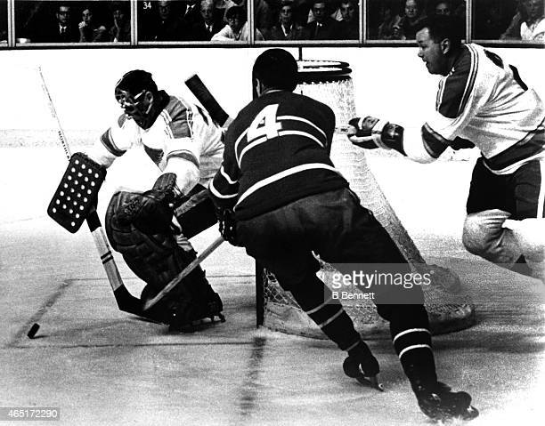 Jean Beliveau of the Montreal Canadiens goes after the puck as his former teammates goalie Jacques Plante and Doug Harvey of the St Louis Blues...
