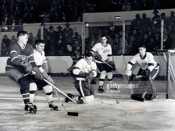 Jean Beliveau of the Montreal Canadiens goes for the puck as Barry Cullen goalie Terry Sawchuk Red Kelly and Alex Delvecchio of the Detroit Red Wings...