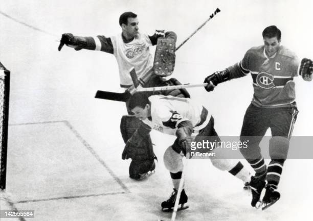 Jean Beliveau of the Montreal Canadiens hits Bryan Watson of the Detroit Red Wings in the head as goalie Roger Crozier of the Red Wings defends the...