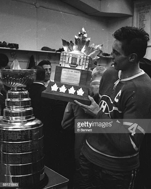 Jean Beliveau of the Montreal Canadiens holds the Conn Smythe Trophy in the locker room after defeating the Chicago Blackhawks in Game 7 of the 1965...