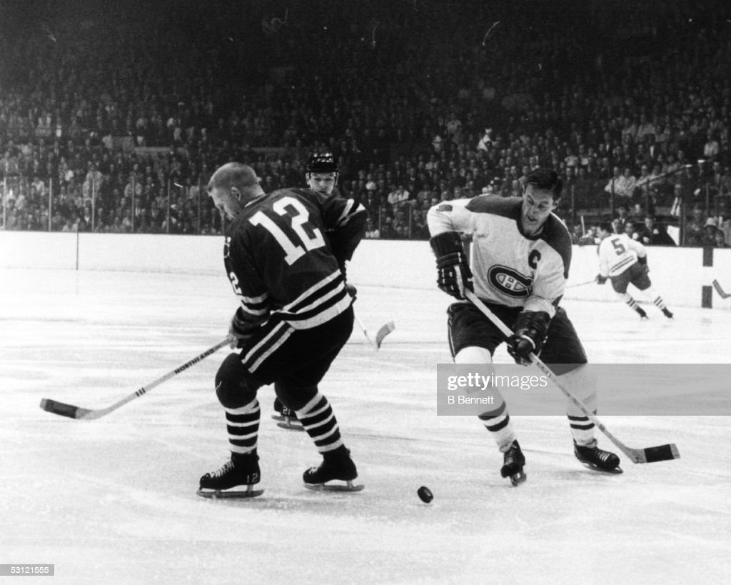 Jean Beliveau #4 of the Montreal Canadiens looks to control the puck as Pat Stapleton #12 of the Chicago Blackhawks over skates it during Game 3 of the 1968 Semi Finals on April 23, 1968 at the Chicago Stadium in Chicago, Illinois.